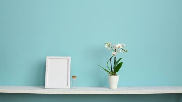 Moderní výzdoba pokojů s obrázkem rámu. Bílá šelba proti pastelové tyrkysové stěně s vroubené orchidejí a ručně položená fialová rostlina.