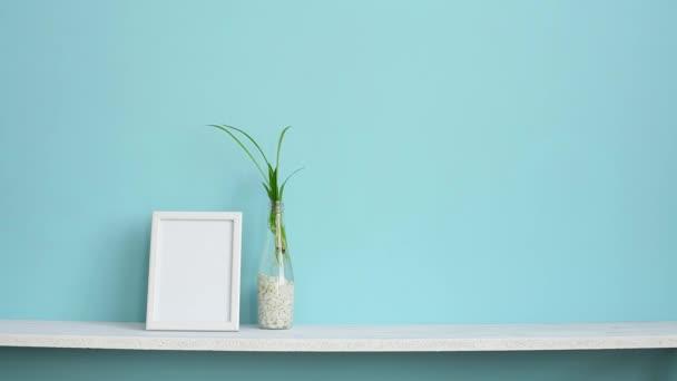 Decorazione moderna della camera con cornice dimmagine mockup. Mensola bianca contro parete turchese pastello con tagli di piante di ragno in acqua e mano mettendo giù il cactus.