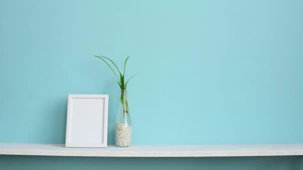 Decorazione moderna della camera con cornice dimmagine mockup. Mensola bianca contro parete turchese pastello con tagli di piante di ragno in acqua e mano mettendo giù succulento.