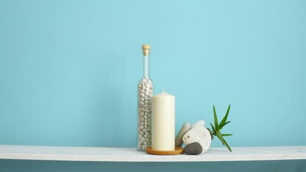 Decorazione moderna della camera con cornice mockup. Mensola bianca contro parete turchese pastello con candela e rocce in bottiglia. Mano mettendo giù cornice vuota.
