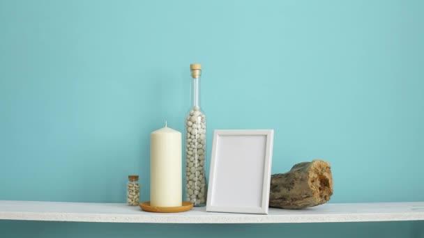 Decorazione moderna della camera con cornice dimmagine mockup. Mensola bianca contro parete turchese pastello con candela e rocce in bottiglia. Mano mettendo giù pianta succulenta in vaso