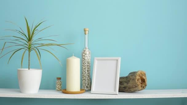 Moderní výzdoba pokojů s obrázkem rámu. Bílá police proti pastelové tyrkysové stěně se svíčkami a balvany v lahvi. Ručně zavlažená drašenská rostlina