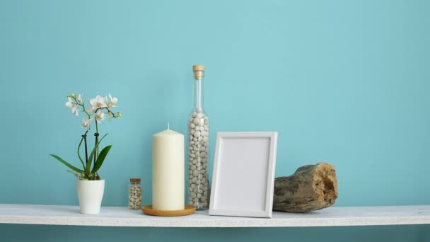 Modern room decoration with Picture frame mockup. White shelf against pastel turquoise wall with Candle and rocks in bottle. Hand watering potted orchid plant