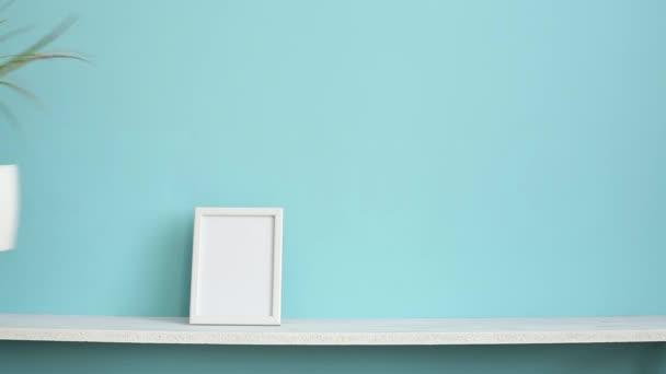 Moderní výzdoba pokojů s obrázkem rámu. Bílá police proti pastelové tyrkysové stěně a ruce, které dávají do květinárny DRACAENA.
