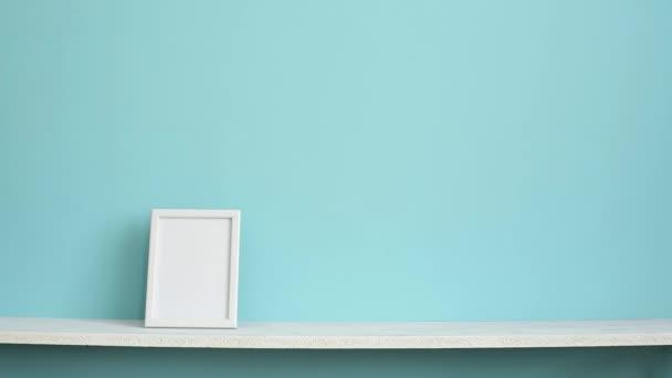 Moderní výzdoba pokojů s obrázkem rámu. Bílá police proti pastelové tyrkysové stěně s rukou položená šťavnaté rostliny.