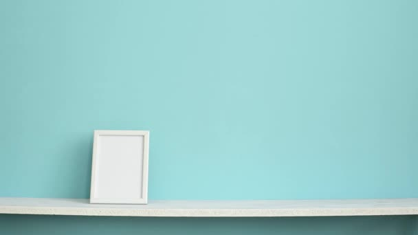 Modern room decoration with Picture frame mockup. White shelf against pastel turquoise wall with hand putting down potted violet plant.