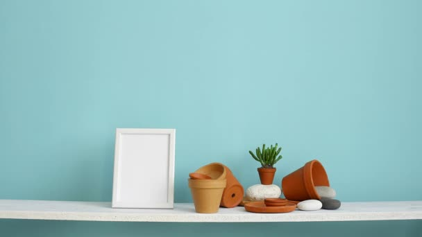Modern room decoration with picture frame mockup. White shelf against pastel turquoise wall with pottery and succulent plant. Hand putting down potted succulent plant.
