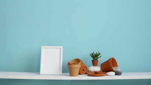 Moderní výzdoba pokojů s obrázkem rámu. Bílá police proti pastelové tyrkysové stěně s keramickými a šťavnaté rostlinnou. Ruční zaskladnění šťavnaté rostliny.