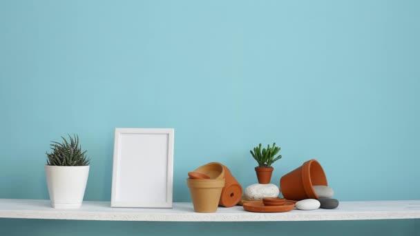 Moderní výzdoba pokojů s obrázkem rámu. Bílá police proti pastelové tyrkysové stěně s keramickými a šťavnaté rostlinnou. Ručně zaléchaná šťavnaté rostlina.