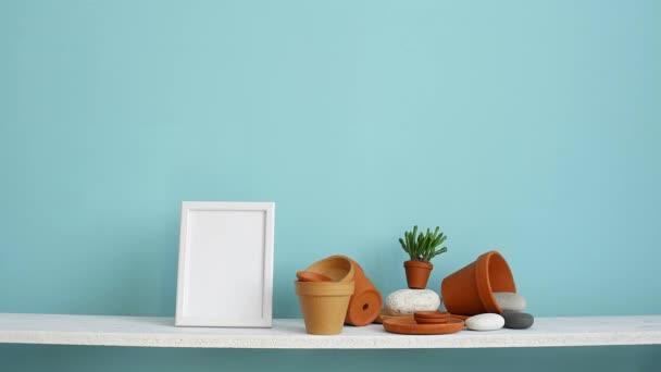 Decorazione moderna della camera con cornice di immagine mockup. Mensola bianca contro parete turchese pastello con ceramica e pianta succulenta. Mano mettendo giù cactus in vaso.