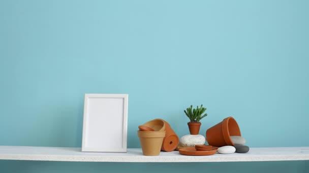 Modern szoba dekoráció képkeret mockup. Fehér polc pasztell türkiz fal kerámia és zamatos növény. Kézzel szállt cserepes kaktusz.