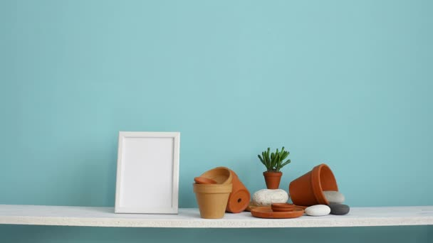 Modern room decoration with picture frame mockup. White shelf against pastel turquoise wall with pottery and succulent plant. Hand putting down potted violet plant.
