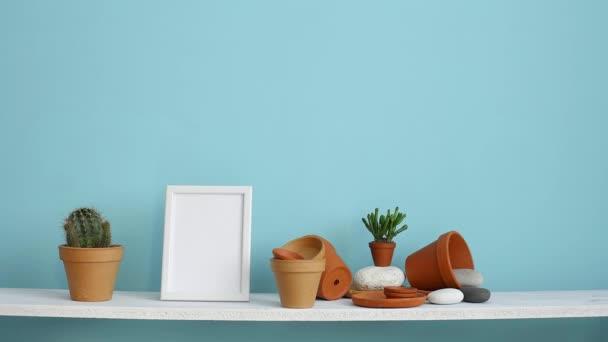 Moderní výzdoba pokojů s obrázkem rámu. Bílá police proti pastelové tyrkysové stěně s keramickými a šťavnaté rostlinnou. Ručně zavlažované kaktusové rostliny.
