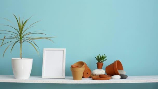 Moderní výzdoba pokojů s obrázkem rámu. Bílá police proti pastelové tyrkysové stěně s keramickými a šťavnaté rostlinnou. Ručně zavlažená drašenská rostlina.
