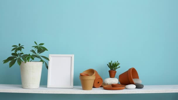 Modern room decoration with picture frame mockup. White shelf against pastel turquoise wall with pottery and succulent plant. Hand watering potted schefflera plant.