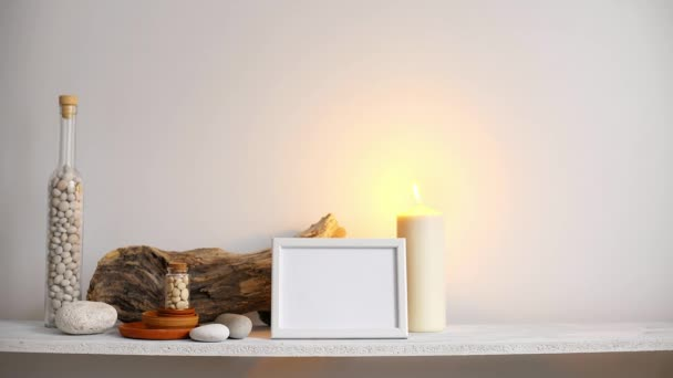 Modern room decoration with picture frame mockup. Shelf against white wall with decorative candle, glass and rocks. Candle burning.