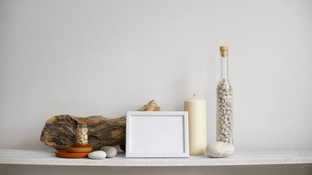 Modern room decoration with picture frame mockup. Shelf against white wall with decorative candle, glass and rocks. Hand putting down potted cactus plant.