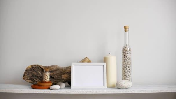 Decorazione moderna della camera con cornice di immagine mockup. Scaffale contro parete bianca con candela decorativa, vetro e rocce. Mano mettendo giù pianta di cactus in vaso.