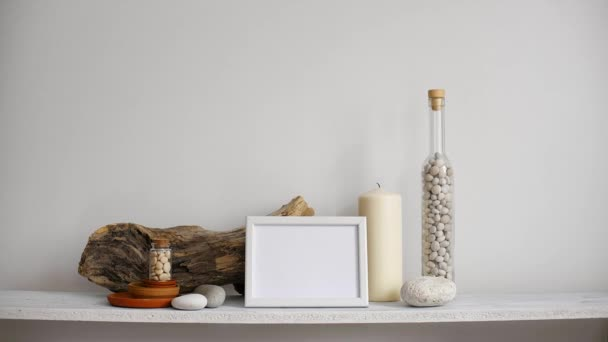 Modern room decoration with picture frame mockup. Shelf against white wall with decorative candle, glass and rocks. Hand putting down potted dracaena plant.