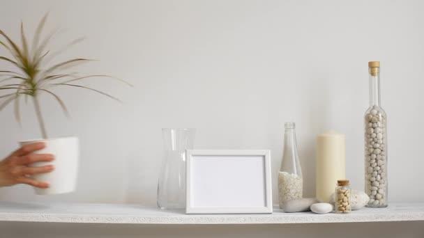 Modern szoba dekoráció képkeret mockup. Polc ellen fehér fal dekoratív gyertya, üveg és szikla. Kézzel szállt cserepes Dracaena növény.