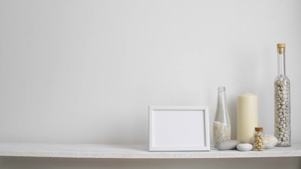 Modern room decoration with picture frame mockup. Shelf against white wall with decorative candle, glass and rocks. Hand putting down potted orchid plant.