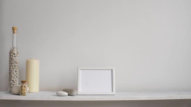 moderne Raumdekoration mit Bilderrahmen-Attrappe. Regal vor weißer Wand mit dekorativer Kerze, Glas und Steinen. Hand legt Topfpflanze nieder.