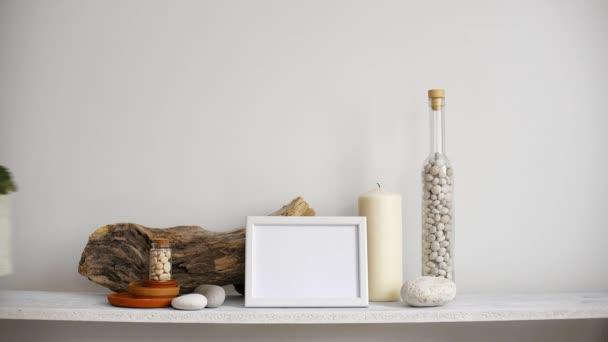 Decorazione moderna della camera con cornice di immagine mockup. Scaffale contro parete bianca con candela decorativa, vetro e rocce. Mano mettendo giù pianta viola in vaso.