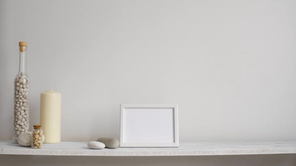 Modern room decoration with picture frame mockup. Shelf against white wall with decorative candle, glass and rocks. Hand putting down potted violet plant.
