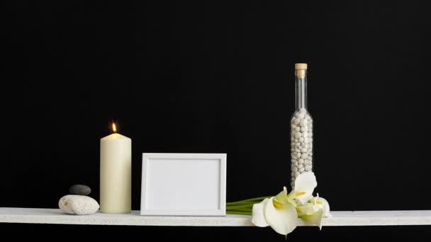Decorazione moderna della camera con cornice di immagine mockup. Scaffale contro parete nera con candela decorativa, vetro e rocce. Candela accesa.