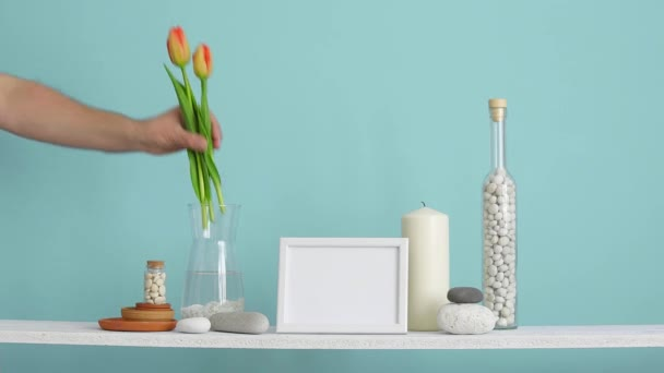 Modern room decoration with picture frame mockup. Shelf against turquoise wall with decorative candle, glass and rocks. Hand putting Tulips in vase.