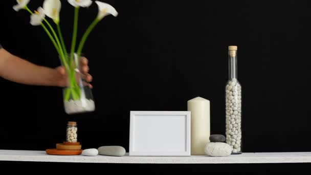 Modern room decoration with picture frame mockup. Shelf against black wall with decorative candle, glass and rocks. Hand putting Tulips in vase.