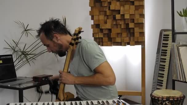 professioneller Musiker im digitalen Studio zu Hause. Er setzt Kopfhörer auf, umgeben von Instrumenten und Midicontroller. Musikproduktionskonzept.