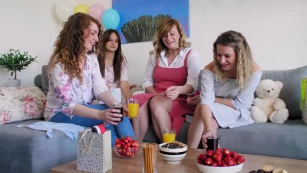 Skupina přátel v obývacím pokoji slaví se svým přítelem, který čeká dítě, zatímco připíjí s džusem. Všichni jsou šťastní a usmívají se, a pokoj je vyzdoben a připraven na oslavu.