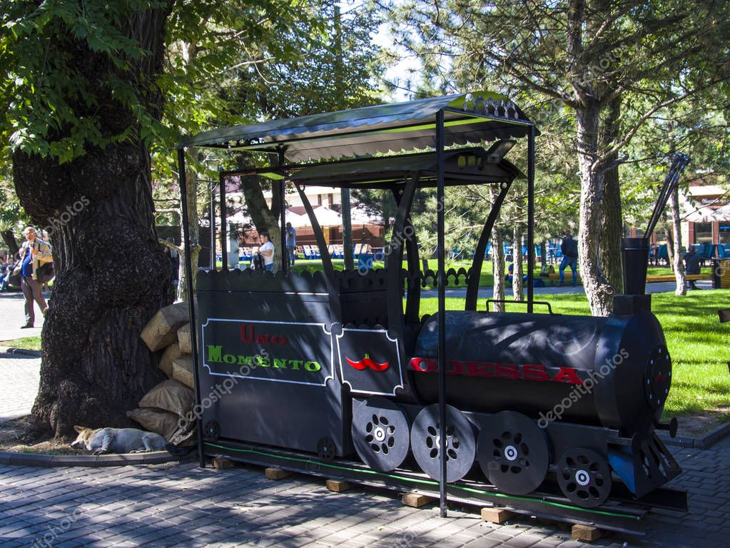 A decorative iron locomotive stands in a park near a thick tree, a dog sleeps under a tree