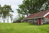starý malý kamenný dům s červenými dveřmi a střecha v Norsku