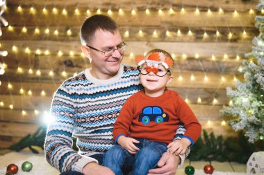 happy Caucasian father with son in Christmas house with illuminated garland and decorated tree