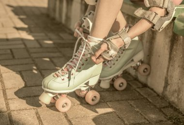 Skater girl putting on mint retro roller skates outdoor - hobby, sports and active lifestyle concept.