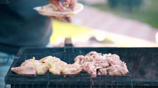 Close-up: Man stands on the background of a summer house lays meat on a barbecue grill, children run alongside.