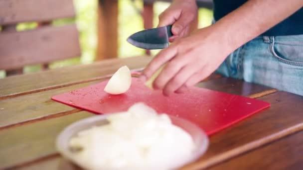 Zblízka: ten chlápek vaří pilaf. Je v letním domě, krájí cibuli na červené střihací desce.