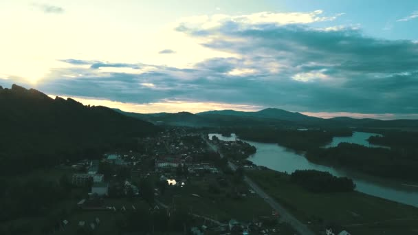 Aerial view: Small tourist town in the mountains, under clouds. In the twilight. Near the mountain river.