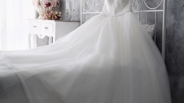 slow motion white wedding dress on bed near nightstand