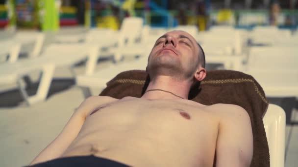 Zblízka: na pláži leží holohlavý italský muž, na sluníčku, opalování.