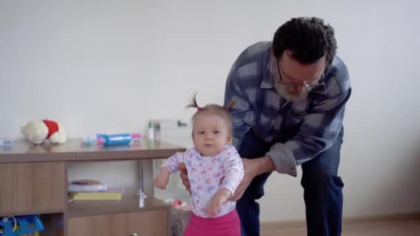 Grandfather with a beard, wearing glasses, playing with a little adorable granddaughter