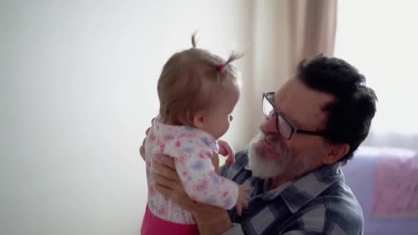 Grandfather with a beard, wearing glasses, playing
