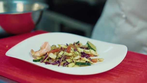 Cook zdobí salát s krevetami