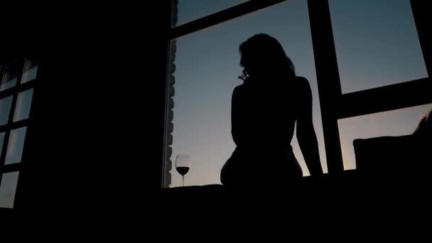 silueta dívka sedící poblíž wineglass na parapetu