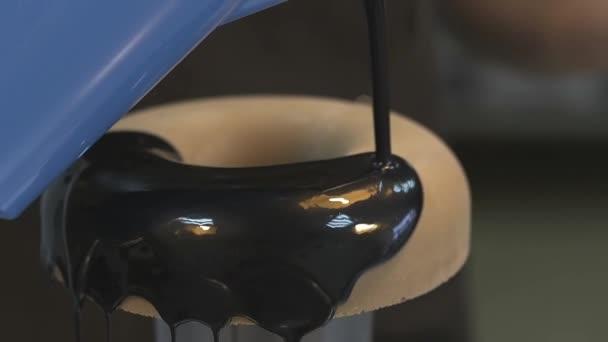cukrář nalévá čokoládovou polevou na velké pečené koblihy