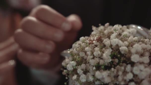 ženich má zásnubní prsten, který leží v květech, během svatebního obřadu, zblízka, pomalý pohyb