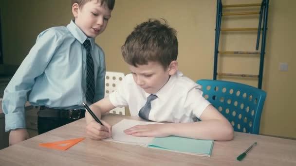A tanulók házi feladatot végeznek, számokat írnak a jegyzetfüzetekbe, egyikük elmagyarázza, hogy mit kell tenni