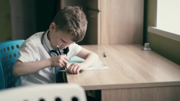 Schoolboy does homework, sits in headphones, draws in a notebook with a triangular yardstick.